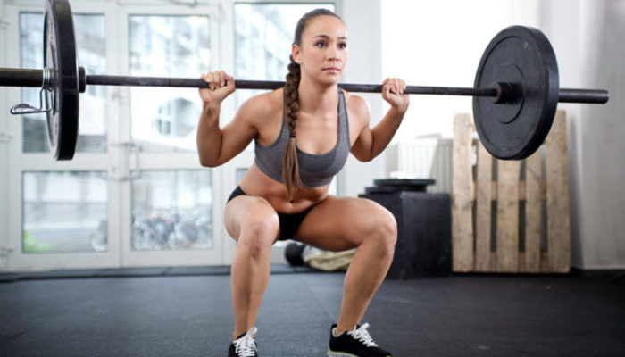 Woman performing a barbell back squat in the gym