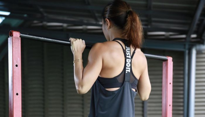 Woman at the top of a pull up