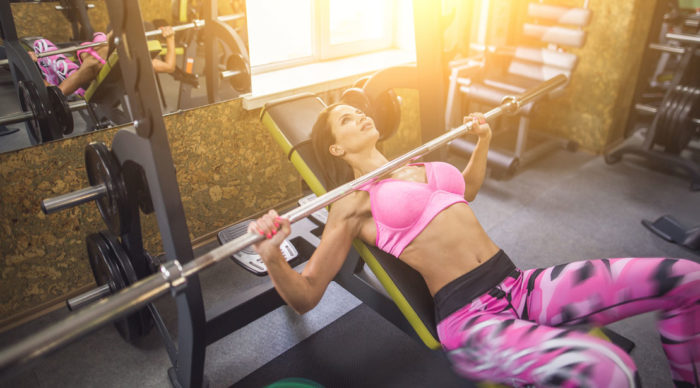 Woman performing an incline bench press with bar