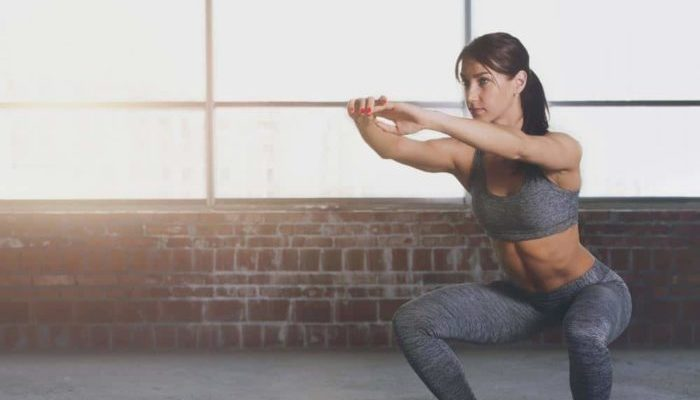 woman performing a bodyweight squat