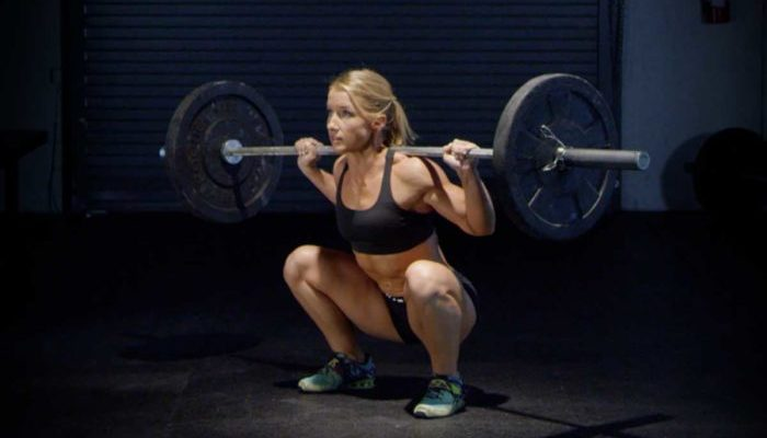 Woman at the bottom of a back squat as part of a legs workout for women
