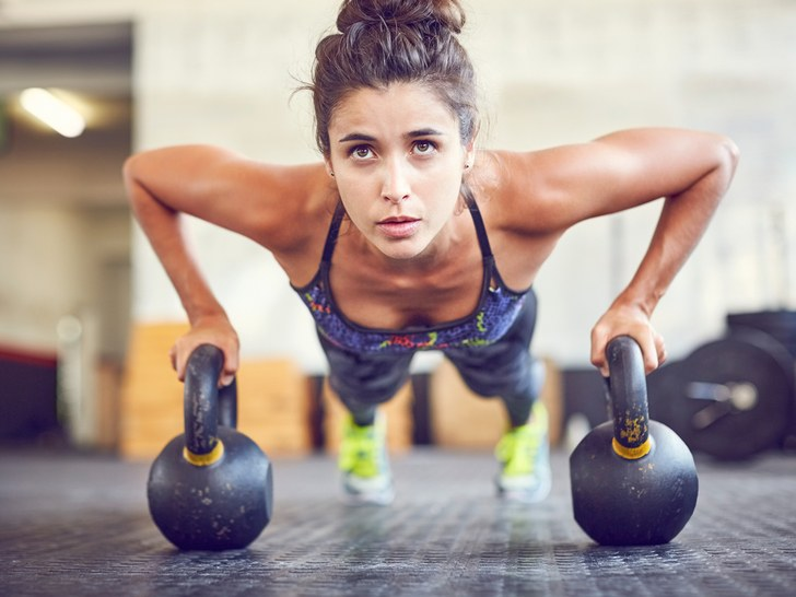 woman performing press ups in a kettlebell workout for women